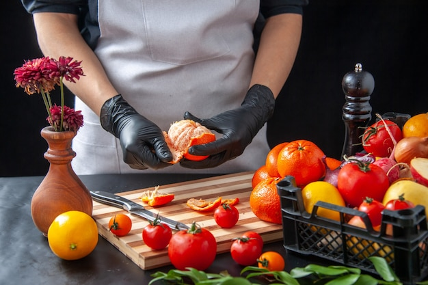 Вид спереди женщина-повар, чистящая мандарины на темноте, кулинария, салат, здоровая диета, овощная еда, еда, фрукты, работа