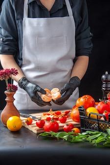 Вид спереди женщина-повар, чистящая мандарины на темном кулинарии, салат, здоровая диета, овощная еда, еда, фрукты, работа