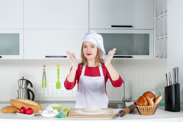 Front view female cook in cook hat and apron clapping her hands in the kitchen