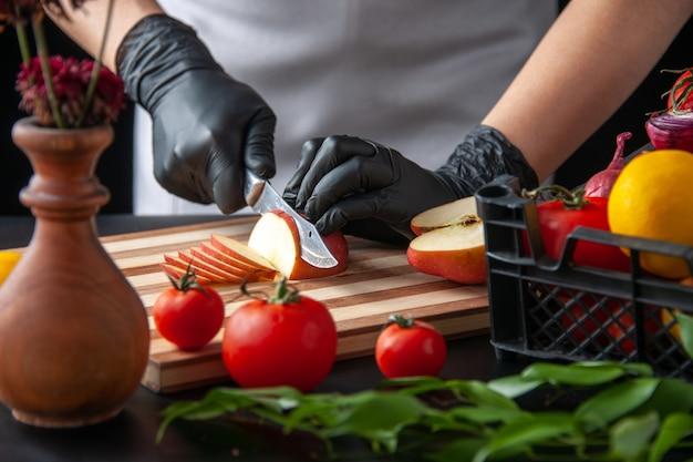 Vista frontale cuoca che taglia mela su un'insalata di cottura scura salute lavoro dieta pasto vegetale cibo frutta
