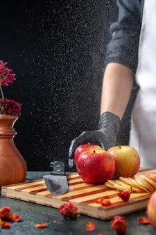 Cuoca vista frontale che taglia mele su una dieta di frutta scura insalata cibo pasto succo esotico lavoro