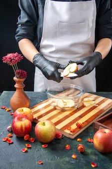 Cuoca di vista frontale che taglia le mele nel piatto su insalata di dieta di frutta scura pasto cibo succo esotico lavoro torta torta