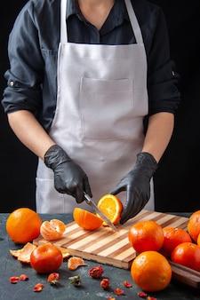 Vista frontale cuoca che taglia l'arancia su una bevanda scura insalata pasto salute cibo lavoro verdura frutta dieta