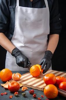Cuoca vista frontale che taglia arancia su bevanda scura insalata pasto salutare cibo verdura frutta dieta
