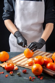 Front view female cook cutting orange on a gray salad health meal food job vegetable fresh drink fruit diet
