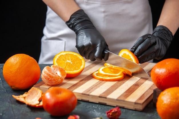 Вид спереди женщина-повар режет апельсин на темном овощном напитке здоровое питание работа фруктовый диетический салат