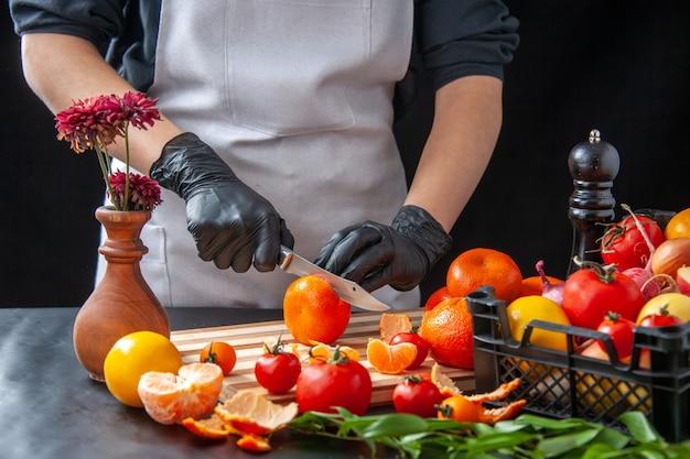 Cuoca vista frontale che taglia mandarini su insalata di cottura scura dieta salute pasto vegetale cibo frutta lavoro