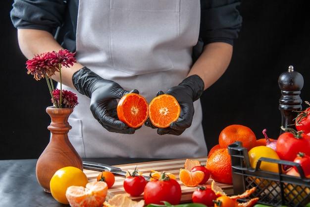 Front view female cook cutting tangerines on dark cooking salad health vegetable meal food fruit job diet