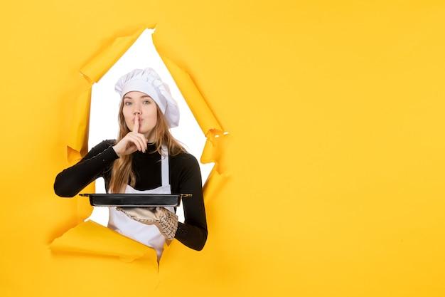 黄色い感情の太陽の食べ物の写真の仕事キッチン料理の色に黒い鍋を保持している正面図の女性料理人