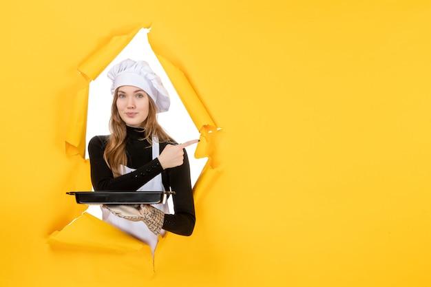 Cuoca vista frontale che tiene in mano una padella nera con biscotti su giallo emozione cibo solare lavoro cucina cucina colore