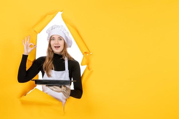 Cuoca vista frontale che tiene in mano una padella nera con biscotti su giallo emozione cibo sole foto lavoro cucina colore