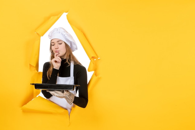 Cuoca vista frontale che tiene in mano una padella nera con biscotti su giallo emozione cibo sole foto lavoro cucina cucina colore