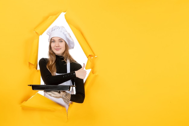 Front view female cook holding black pan with biscuits on yellow emotion sun food photo job kitchen cuisine colors