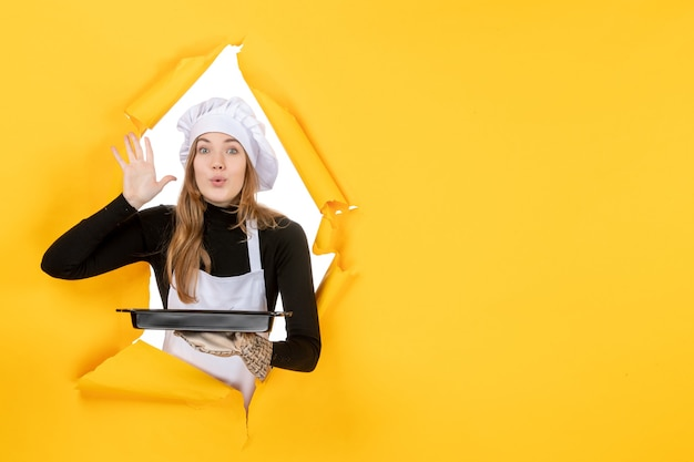 Front view female cook holding black pan with biscuits on yellow photo emotion sun food kitchen cuisine color job