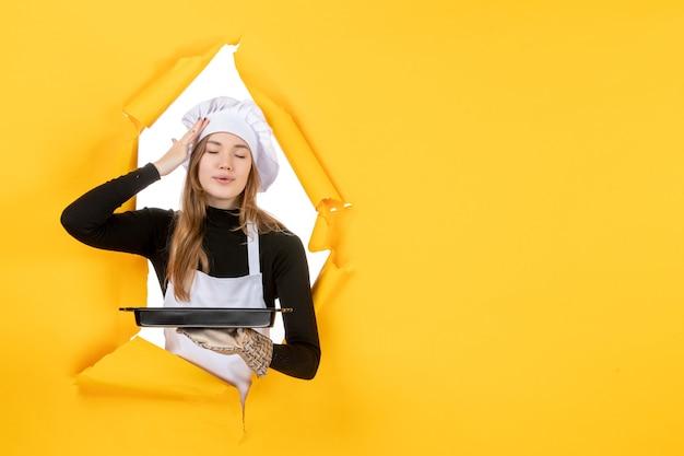 Cuoca vista frontale che tiene in mano una padella nera su giallo emozione cibo solare lavoro cucina cucina colore