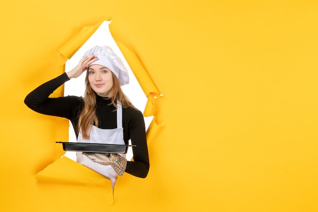 Cuoca vista frontale che tiene in mano una padella nera su giallo emozione cibo solare foto lavoro cucina colore