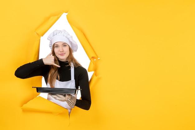 Cuoca vista frontale che tiene padella nera su emozione gialla cibo solare lavoro fotografico cucina cucina colore