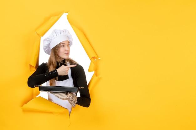 Cuoca vista frontale che tiene padella nera su emozione gialla cibo solare lavoro fotografico cucina cucina colori