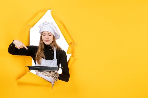 Cuoca vista frontale che tiene padella nera su emozione gialla cibo solare lavoro fotografico cucina cucina