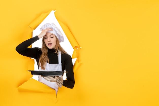 Cuoca vista frontale che tiene in mano una padella nera su giallo emozione cibo solare foto cucina cucina colore
