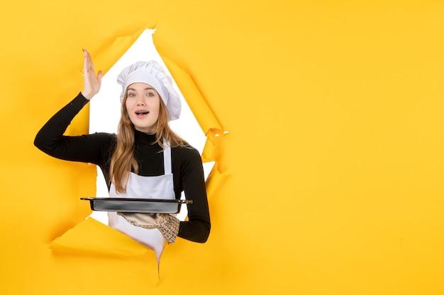 Cuoca vista frontale che tiene padella nera su emozioni gialle cibo solare lavoro fotografico cucina cucina colore