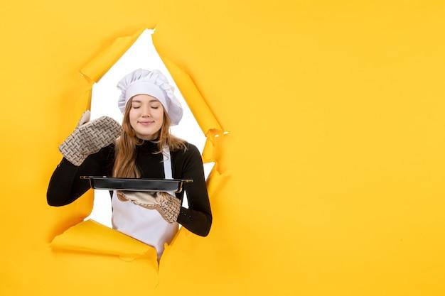 Cuoca vista frontale che tiene una padella nera su giallo sole tempo cibo foto lavoro cucina emozione cucina colori