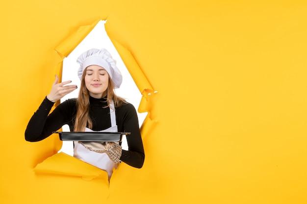 Cuoca vista frontale che tiene in mano una padella nera su giallo sole tempo cibo foto lavoro cucina emozione cucina