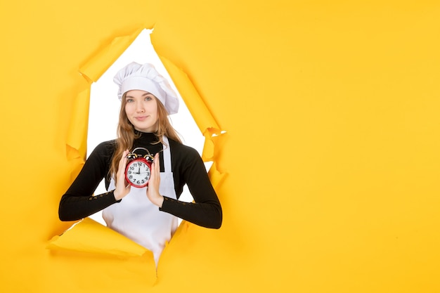 Front view female cook holding clock on the yellow photo color job cuisine kitchen sun food emotion time