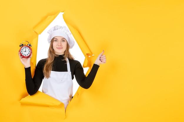 黄色の時間に時計を保持している正面の女性料理人食べ物写真仕事キッチン太陽料理色