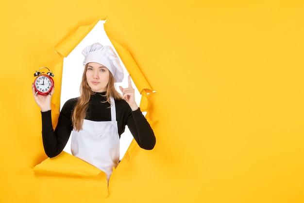黄色の時間に時計を保持している正面の女性料理人食べ物写真キッチン感情太陽料理色