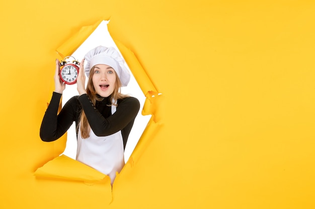 Front view female cook holding clocks on yellow food photo color job cuisine kitchen emotion time sun