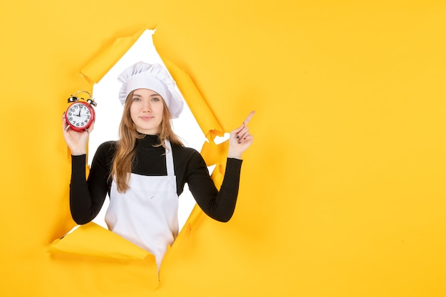 Front view female cook holding clocks on yellow food photo color job cuisine kitchen emotion time