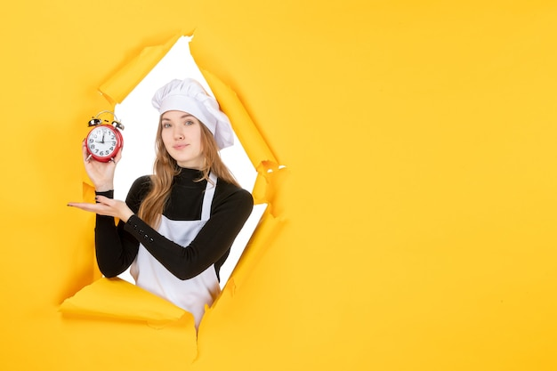 Front view female cook holding clocks on yellow food photo color job cuisine kitchen emotions time sun