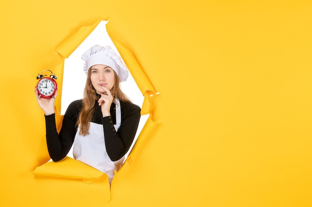 Front view female cook holding clocks on yellow food photo job kitchen emotion sun cuisine color