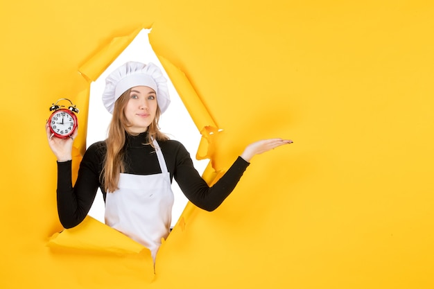 Front view female cook holding clocks on yellow time food color job kitchen emotion sun cuisine