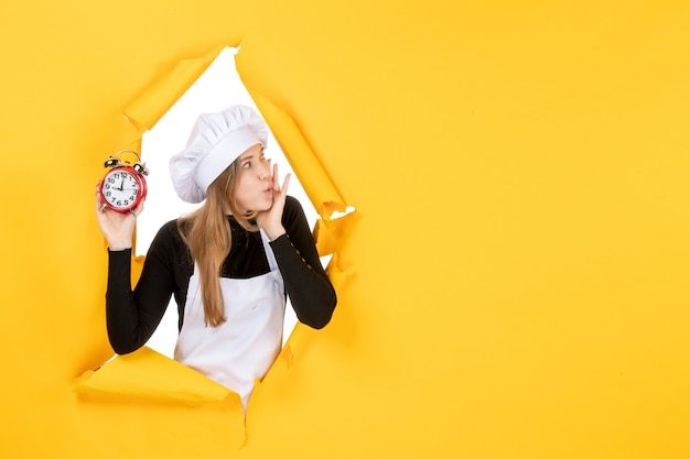 Front view female cook holding clocks on a yellow time food photo color job kitchen emotion sun cuisine