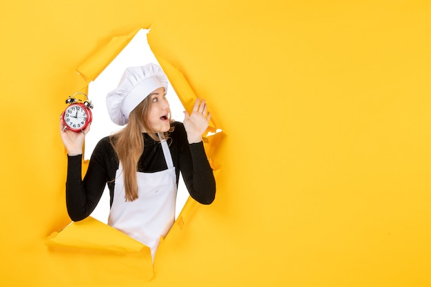 Front view female cook holding clocks on yellow time food photo color job kitchen emotion sun cuisine