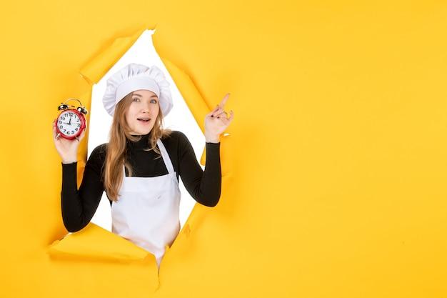 Cuoca vista frontale che tiene gli orologi sul tempo giallo cibo foto colore lavoro cucina emozione sun