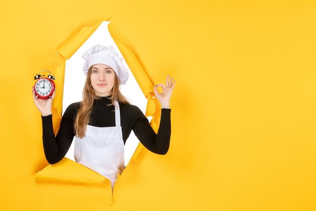 Front view female cook holding clocks on yellow time food photo job emotion sun cuisine color