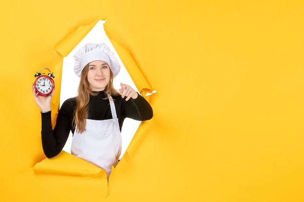 Front view female cook holding clocks on yellow time food photo job kitchen emotion cuisine color