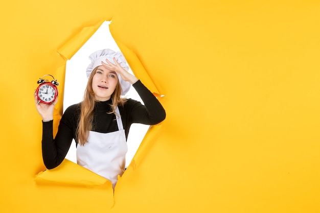 Front view female cook holding clocks on yellow time food photo job kitchen emotion sun color