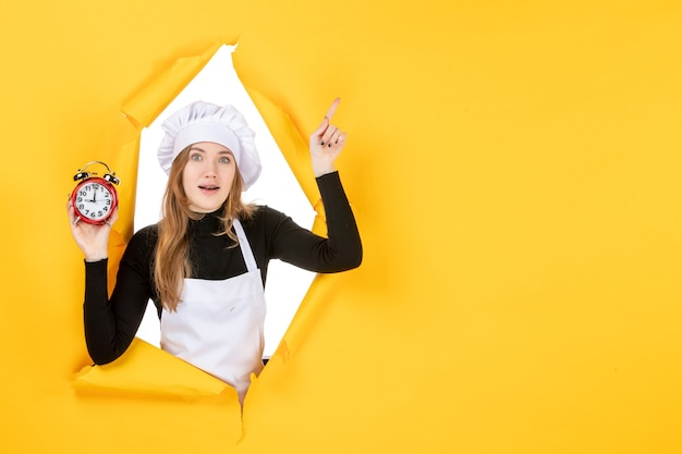 Front view female cook holding clocks on yellow time food photo job kitchen emotion sun cuisine color
