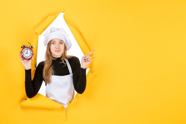 Front view female cook holding clocks on yellow time food photo job kitchen emotion sun cuisine