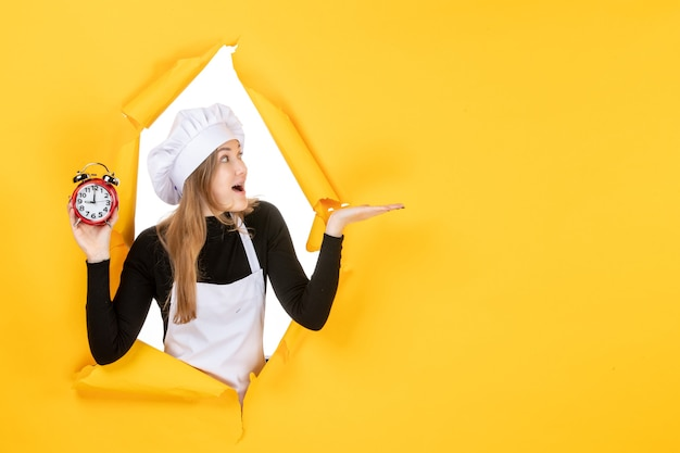 Front view female cook holding clocks on yellow time photo color job kitchen emotion sun cuisine