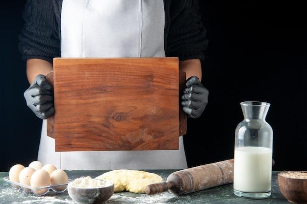 ダークケーキパイカラークッキングベイクビスケット生地の仕事の机の上に机を保持している正面の女性の料理人