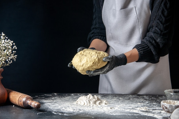 Cuoca vista frontale che tiene la pasta su pasta scura uovo lavoro panetteria hotcake pasticceria cucina cucina