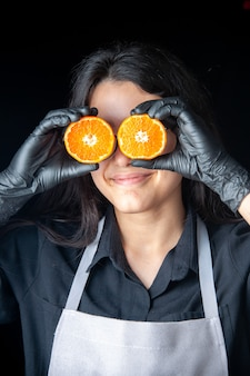 Front view female cook holding half sliced tangerines to her eyes on a dark cooking salad health vegetable meal food fruit job diet