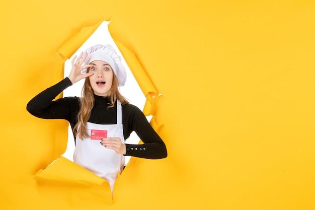 黄色の仕事の写真に赤い銀行カードを保持している正面の女性料理人感情食品キッチン色お金料理