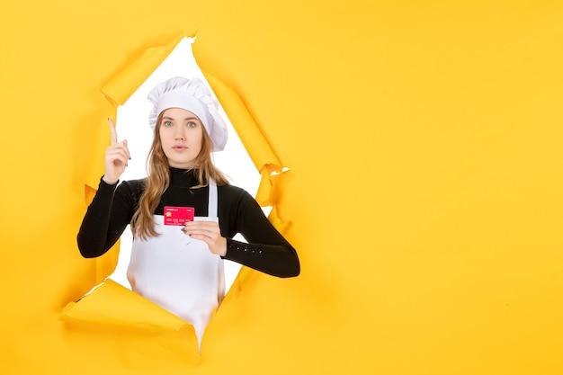 黄色の写真に赤い銀行カードを保持している正面図の女性料理人感情食品キッチン料理お金の仕事