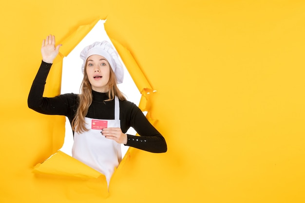 Front view female cook holding red bank card on yellow emotion money food kitchen cuisine color job